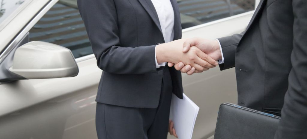 Business People Shaking Hands By Car thumbnail